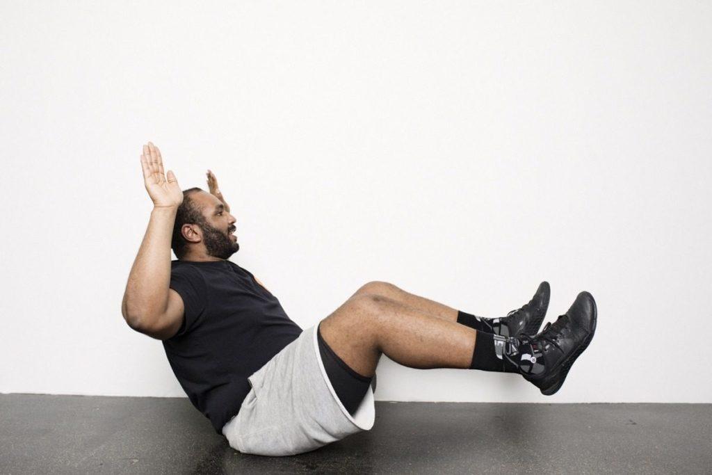 Personal Trainer zeigt Fitnessübung für Bauch